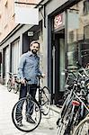 Portrait of happy mid adult male owner standing outside bicycle repair shop