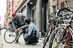 Young man explaining bicycle problems to repairman outside workshop