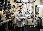 Portrait of mid adult male owner standing arms crossed at bicycle repair shop