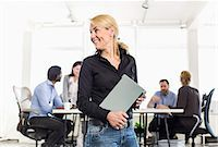 five - Mature businesswoman looking away while holding laptop with colleagues sitting at desk in background Stock Photo - Premium Royalty-Freenull, Code: 698-06966513
