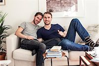 Portrait of homosexual couple sitting together on sofa at home Stock Photo - Premium Royalty-Freenull, Code: 698-06966671