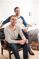 Portrait of happy homosexual couple sitting on chair in bedroom Stock Photo - Premium Royalty-Freenull, Code: 698-06966672