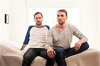 Portrait of homosexual couple sitting on bed at home Stock Photo - Premium Royalty-Freenull, Code: 698-06966673