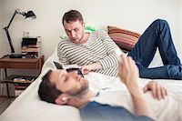 Young gay man reading book with partner listening music on bed at home Stock Photo - Premium Royalty-Freenull, Code: 698-06966674