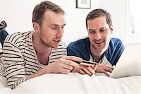 Homosexual couple shopping online on laptop together while lying in bed at home Stock Photo - Premium Royalty-Freenull, Code: 698-06966676
