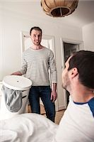 Young gay man looking at partner while holding laundry basket at home Stock Photo - Premium Royalty-Freenull, Code: 698-06966679