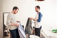 Side view of homosexual couple holding shirts in bedroom Stock Photo - Premium Royalty-Freenull, Code: 698-06966680
