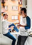 Young homosexual couple having breakfast together by window at home Stock Photo - Premium Royalty-Freenull, Code: 698-06966698