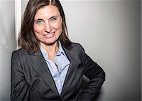 Portrait of mature businesswoman leaning on wall in office Stock Photo - Premium Royalty-Freenull, Code: 698-06966819