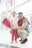 people on mall - Father kneels with younger daughter holding balloon Stock Photo - Premium Royalty-Freenull, Code: 693-06967372