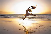 Young woman dancing on sunlit beach Stock Photo - Premium Royalty-Freenull, Code: 614-06973611