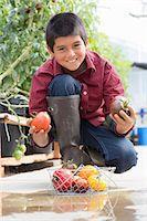 farm and boys - Boy crouching holding ripe tomatoes Stock Photo - Premium Royalty-Freenull, Code: 614-06974035