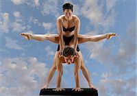 flexible (people or objects with physical bendability) - Mid adult dancers balancing on top of each other against blue sky Stock Photo - Premium Royalty-Freenull, Code: 614-06974607