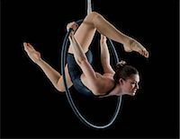 stretching (people exercising) - Aerialist performing on hoop in front of black background Stock Photo - Premium Royalty-Freenull, Code: 614-06974627