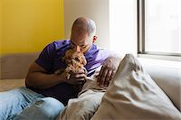 dog kissing man - Mid adult male sitting on sofa with dog Stock Photo - Premium Royalty-Freenull, Code: 614-06974761
