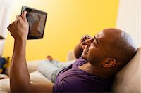 Mid adult male on sofa holding digital tablet and mobile phone Stock Photo - Premium Royalty-Freenull, Code: 614-06974768