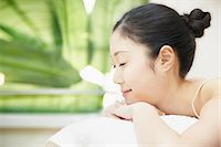 Woman with hair bun lying on front Stock Photo - Premium Royalty-Freenull, Code: 614-06974856