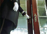 services - Doorman opening hotel door, mid section Stock Photo - Premium Royalty-Freenull, Code: 6106-06976826