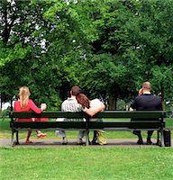 people sitting on bench - Four people sitting on park bench, rear view Stock Photo - Premium Royalty-Freenull, Code: 6106-06976955