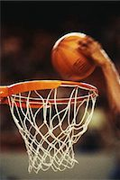 Basketball player slam-dunking ball, close-up of hoop (blurred motion) Stock Photo - Premium Royalty-Freenull, Code: 6106-06976976