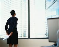 Businesswoman looking out of office window, rear view Stock Photo - Premium Royalty-Freenull, Code: 6106-06977167