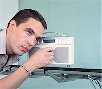 Man adjusting tuning radio Stock Photo - Premium Royalty-Freenull, Code: 6106-06977171