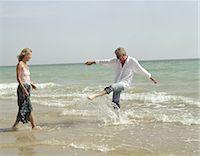 Mature couple playing on beach, man splashing in surf Stock Photo - Premium Royalty-Freenull, Code: 6106-06977202