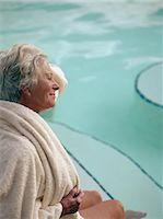 Senior woman sitting beside pool, wrapped in towel, side view Stock Photo - Premium Royalty-Freenull, Code: 6106-06977267
