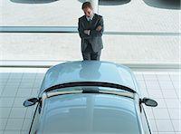 Salesman standing between pillar and car in showroom, elevated view Stock Photo - Premium Royalty-Freenull, Code: 6106-06977278
