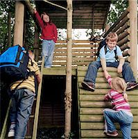 Four children (5-8) playing in tree house Stock Photo - Premium Royalty-Freenull, Code: 6106-06977282