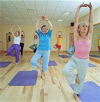 Yoga class, senior woman in centre, smiling Stock Photo - Premium Royalty-Free, Artist: Ikon Images, Code: 6106-06977303