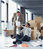 Businessman sitting against box showing colleague paperwork Stock Photo - Premium Royalty-Freenull, Code: 6106-06977411