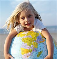 Girl (2-4) on beach resting on inflatable globe, smiling, portrait Stock Photo - Premium Royalty-Freenull, Code: 6106-06977441