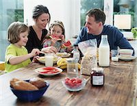 Parents and children (4-6) at table having breakfast Stock Photo - Premium Royalty-Freenull, Code: 6106-06977456