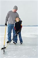 Father and son (4-6) playing ice hockey on frozen lake Stock Photo - Premium Royalty-Freenull, Code: 6106-06977593