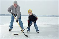 Father and son (4-6) playing ice hockey on frozen lake, portrait Stock Photo - Premium Royalty-Freenull, Code: 6106-06977594