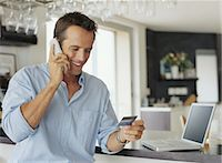 person on phone with credit card - Man by laptop computer, using telephone, holding credit card, smiling Stock Photo - Premium Royalty-Freenull, Code: 6106-06977678