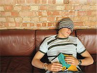 Teenage boy (16-18) wearing hat pulled over eyes, leaning back on sofa Stock Photo - Premium Royalty-Freenull, Code: 6106-06977701