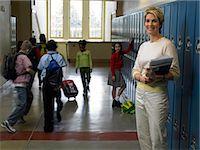 Teacher standing in busy school hallway, portrait Stock Photo - Premium Royalty-Freenull, Code: 6106-06977765