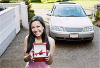 Teenage girl (14-16) standing in driveway, holding car keys with bow Stock Photo - Premium Royalty-Freenull, Code: 6106-06977899