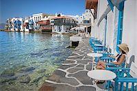 Greece, Mykonos, Little Venice, woman sitting near water Stock Photo - Premium Royalty-Freenull, Code: 6106-06978031