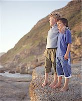 Two boys (6-8) standing arm in arm on large rock outdoors Stock Photo - Premium Royalty-Freenull, Code: 6106-06978243