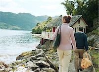 Couple walking towards house by water, rear view Stock Photo - Premium Royalty-Freenull, Code: 6106-06978286