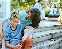 preteen long hair - Mother sitting with son (9-11) on decking Stock Photo - Premium Royalty-Freenull, Code: 6106-06978665