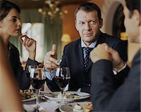 Two businessmen and businesswoman at restaurant table, close-up Stock Photo - Premium Royalty-Freenull, Code: 6106-06978796