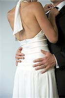 Bride adjusting groom's bow tie, mid section Stock Photo - Premium Royalty-Freenull, Code: 6106-06978843