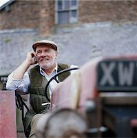 farm phone - Senior male farmer driving tractor, using mobile phone, smiling Stock Photo - Premium Royalty-Freenull, Code: 6106-06978884