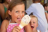 Girl (6-8) eating ice cream, smiling, close-up, portrait Stock Photo - Premium Royalty-Freenull, Code: 6106-06978895