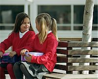 school girl uniforms - Two girls (6-8) sitting on bench holding lunch boxes Stock Photo - Premium Royalty-Freenull, Code: 6106-06978901