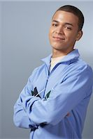 Teenage boy (16-18) against blue background, arms folded, portrait Stock Photo - Premium Royalty-Freenull, Code: 6106-06978947